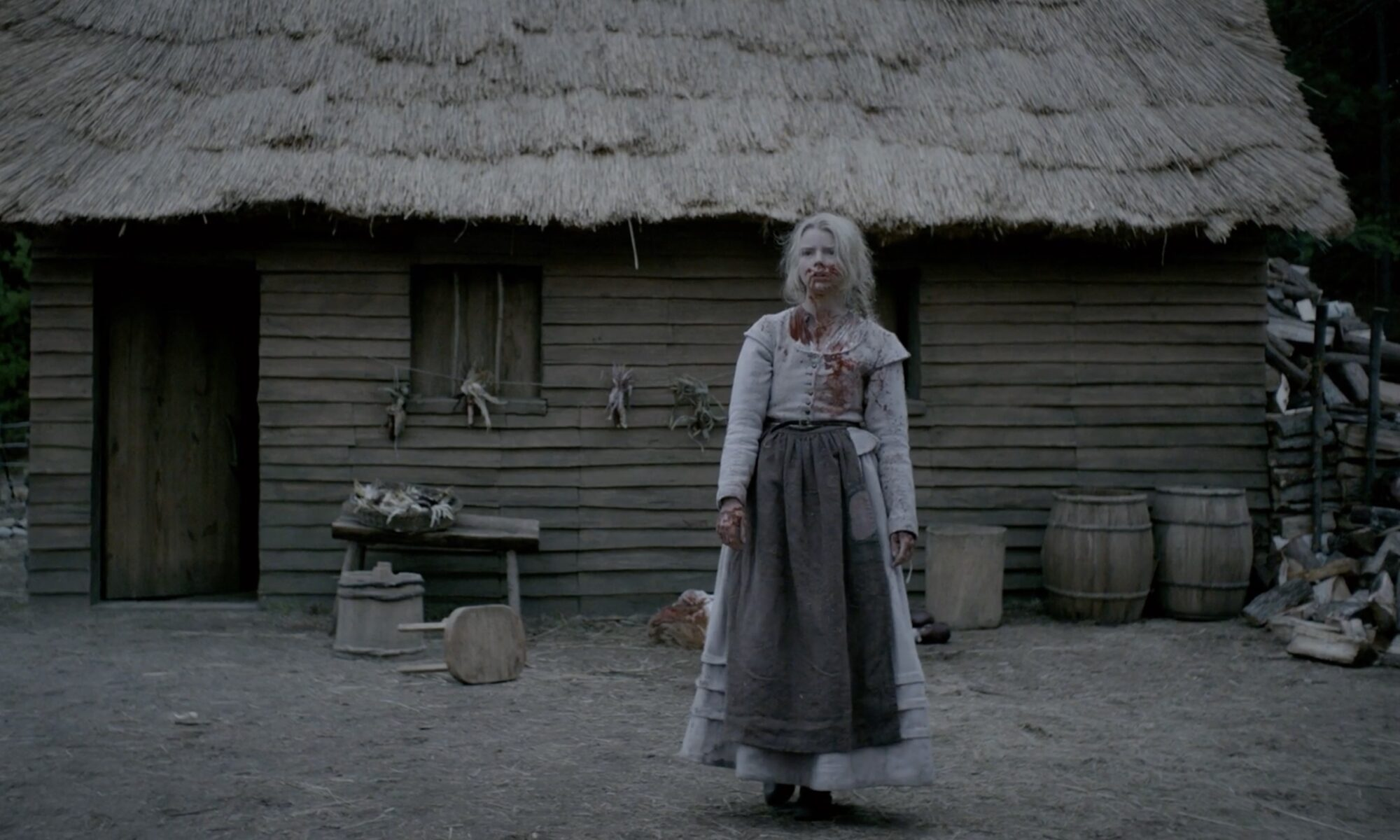 Scene from The Witch of Thomasin, a teenage girl dressed in 15th century clothing, standing alone and bloodied in front of a cabin
