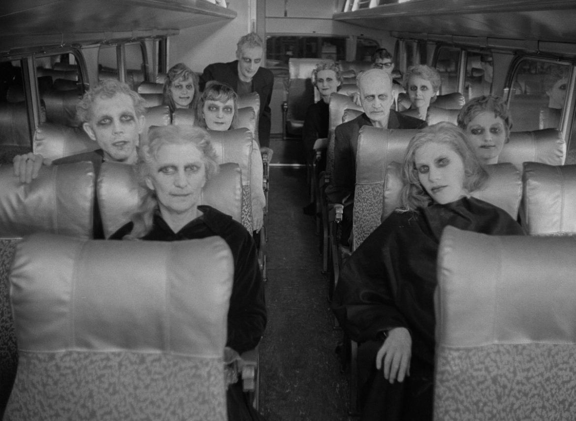 many pale-faced ghouls seated on a bus